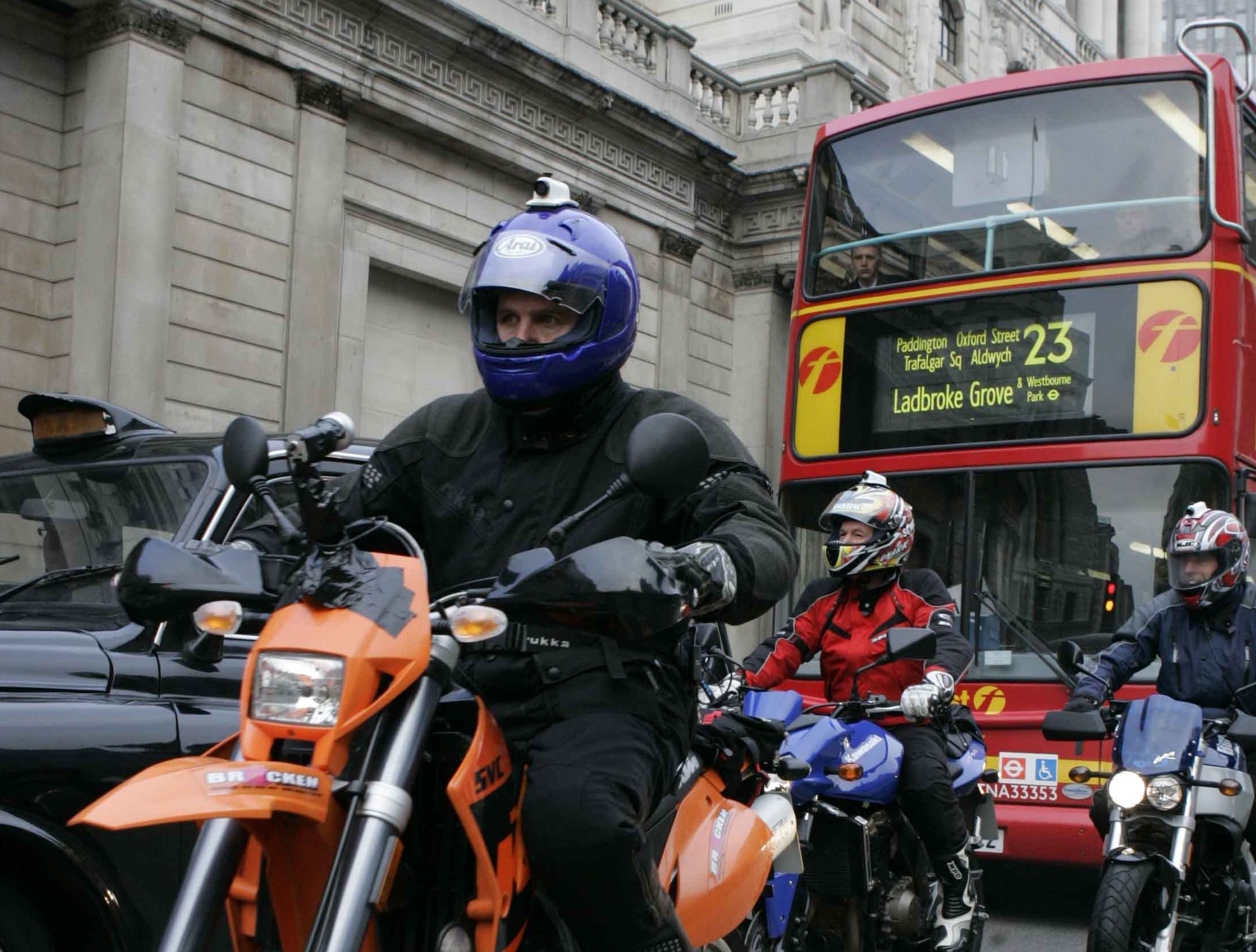 three motorcyclists with bus and taxi in London