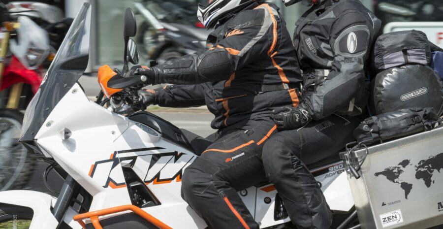 Two people on a KTM motorcycle